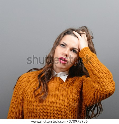 Portrait of forgetful young woman against gray background - stock photo