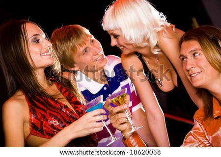 Portrait of four attractive people interacting in the nightclub