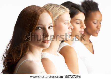 Portrait Of Four Attractive Young Women In Studio Standing In Line - stock photo