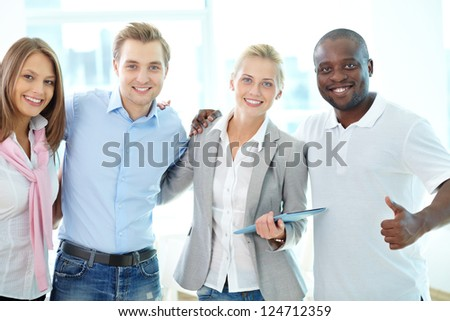 Portrait of four business partners looking at camera with smiles - stock photo