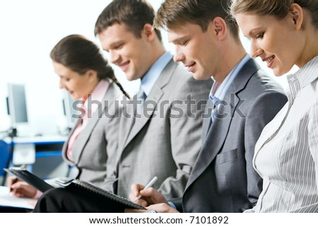 Portrait of four business people reading a text