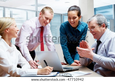 Portrait of four businesspeople discussing computer work in the office - stock photo