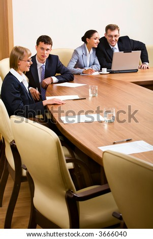 Portrait of four businesspeople discussing different questions sitting in conference room around the table with an opened laptop, documents and glasses of water on it