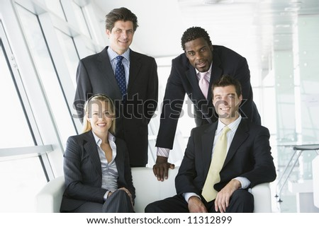 Portrait of four businesspeople in office - stock photo