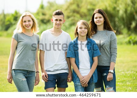 Portrait of four cheerful russian teenagers standing and holding thumbs up together outdoors