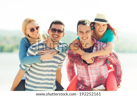 Portrait of four cheerful young friends enjoying summertime on the beach - stock photo