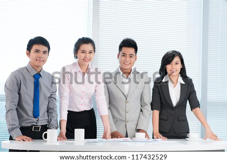 Portrait of four fellow entrepreneurs smiling with enthusiasm - stock photo