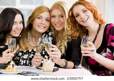 Portrait of four girlfriends holding beverages and looking at camera
