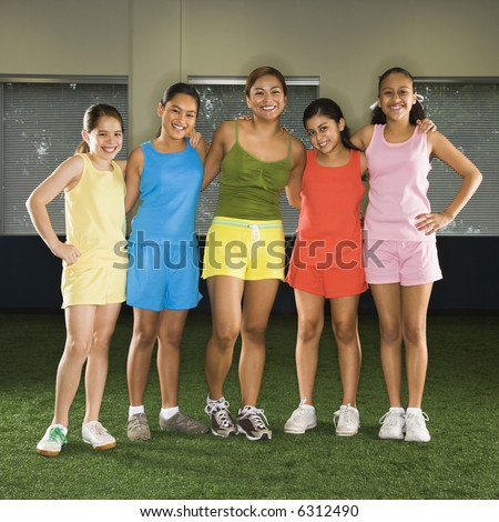 Portrait of four girls and one woman standing together smiling in indoor gym. - stock photo