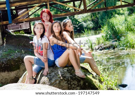 portrait of four girls friends young women having fun sitting on stone posing & looking at camera on summer outdoors copy space background