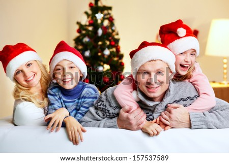 Portrait of four happy family members in Santa caps looking at camera with smiles - stock photo