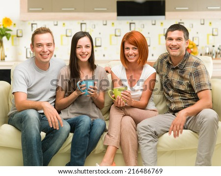 portrait of four happy young caucasian people sitting on couch smiling - stock photo