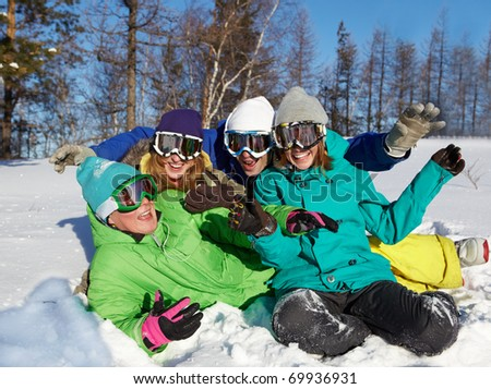 Portrait of four laughing teenagers in ski goggles sitting on snow