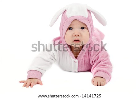 Portrait of four month baby lying on the floor wearing bunny suit isolated on white