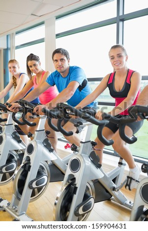 Portrait of four people working out at a class in gym