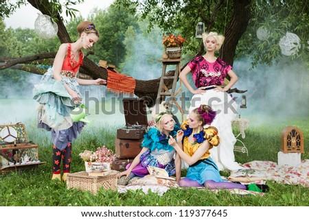 Portrait of four romantic women on a picnic in a fairy forest. Outdoors. - stock photo