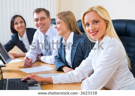 Portrait of four smiling discussing businesspeople sitting at the table in a row with an opened laptops and documents on it - stock photo