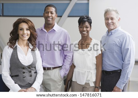 Portrait of four smiling multiethnic businesspeople in office