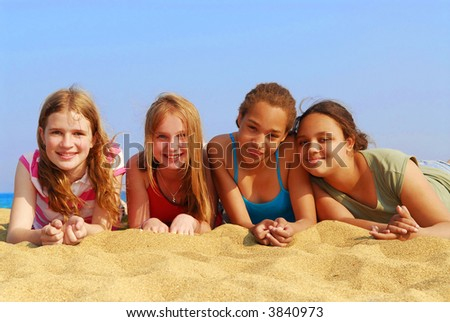 Portrait of four smiling teenage girls on a sandy beach