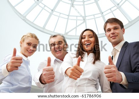 Portrait of four successful business people showing thumbs up and looking at camera - stock photo