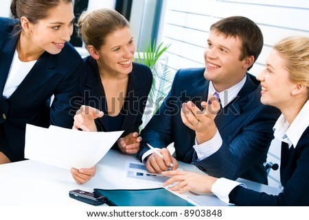 Portrait of four successful people gathered together around the table and discussing a new business-strategy in the office