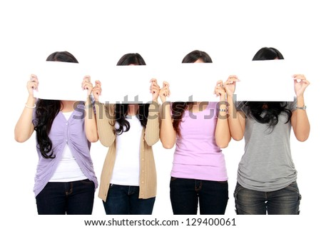 portrait of four teenage girls holding a white board and cover their faces - stock photo