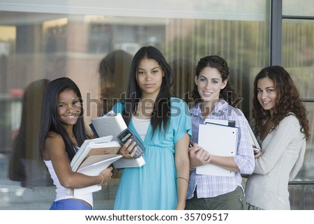 Portrait of four teenage girls holding books and hanging out in the school campus