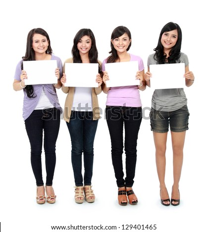 portrait of four teenage girls standing and holding a white board - stock photo