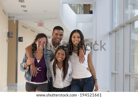 Portrait of four university students smiling in a college hallway - stock photo