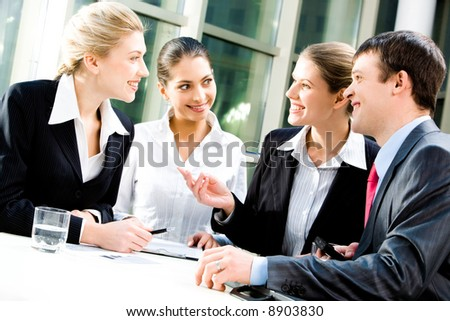 Portrait of four white collar workers discussing a new plan