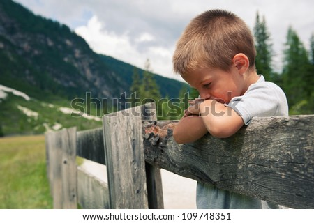 Portrait of four year old boy outdoors in the mountains. Dolomites, Italy. - stock photo