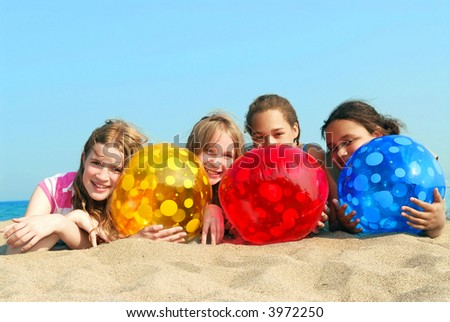 Portrait of four young girls with colorful beach balls - stock photo