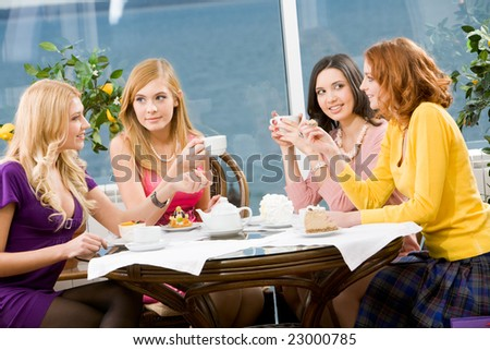 Portrait of four young women sitting at the table in the cafe