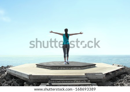 Portrait of free woman raising arms to clear blue sky - stock photo