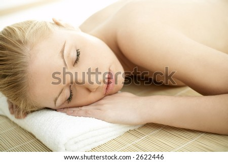 Portrait of Fresh and Beautiful blond woman laying on bamboo mat