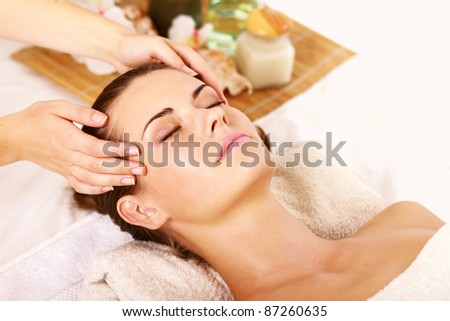 Portrait of Fresh and Beautiful brunette woman taking head massage isolated on white background - stock photo