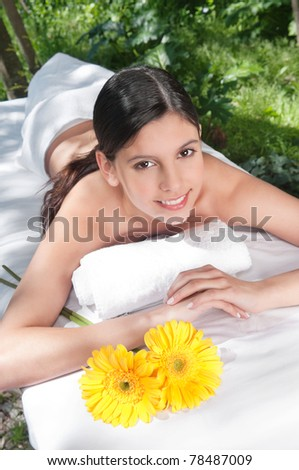 Portrait of fresh and beautiful young woman with flowers around - stock photo