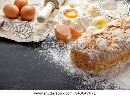 portrait of fresh homemade bakery with ingredients on black board with copy space - stock photo