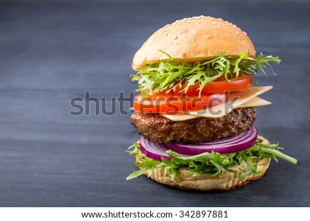 portrait of fresh homemade hamburger on black board for background with copy space