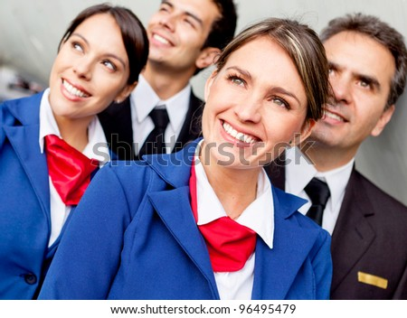 Portrait of friendly airplane cabin crew looking happy - stock photo