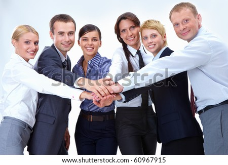 Portrait of friendly business team keeping their hands on top of each other and looking at camera - stock photo