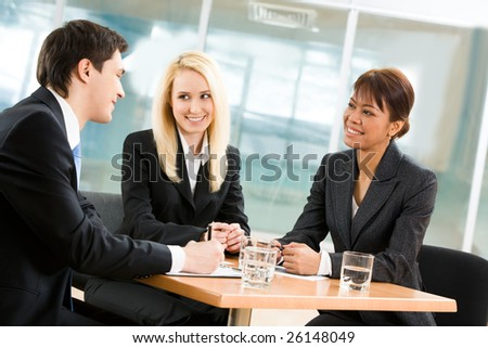 Portrait of friendly business team sitting around table and communicating in office - stock photo