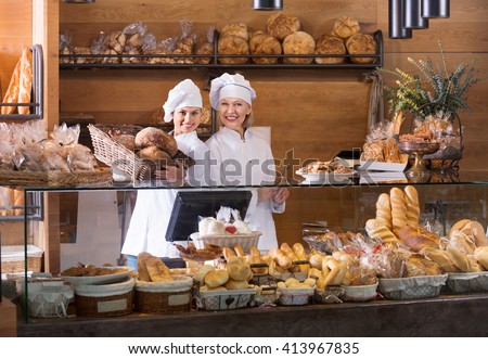 Portrait of friendly cheerful positive women at bakery display with pastry - stock photo