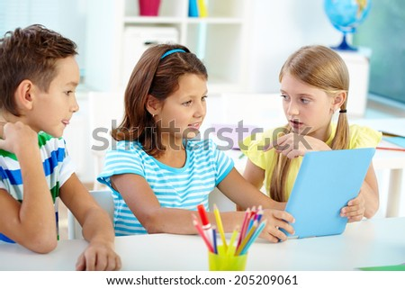 Portrait of friendly classmates at workplace using digital tablet - stock photo
