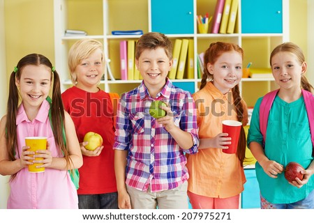 Portrait of friendly classmates with drinks and green apples looking at camera - stock photo