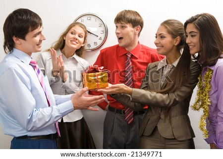 Portrait of friendly colleagues giving birthday present to happy man in office - stock photo