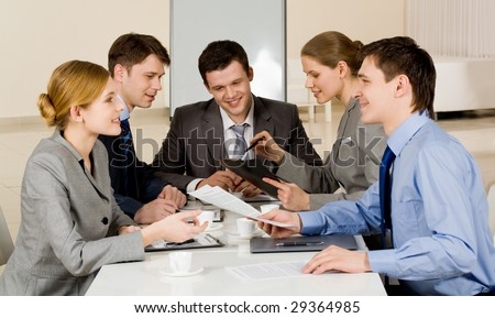 Portrait of friendly colleagues looking at each other while confident woman sharing her idea with co-workers on background