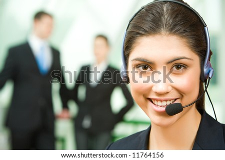 Portrait of friendly consultant with headset on the background of people - stock photo