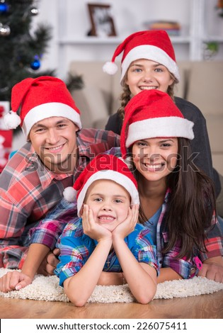 Portrait of friendly family are looking at camera on Christmas evening. Christmas Tree. Santa Hat.
