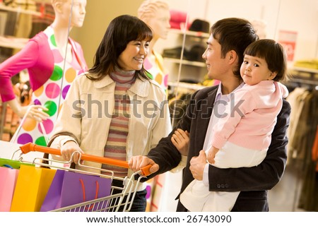 Portrait of friendly family shopping together with shop window at background - stock photo